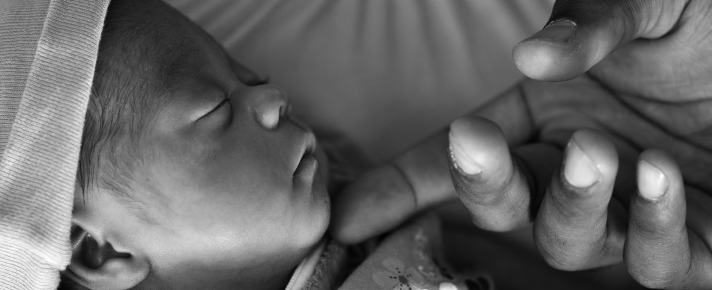 An adult hand gently touching a newborn's face