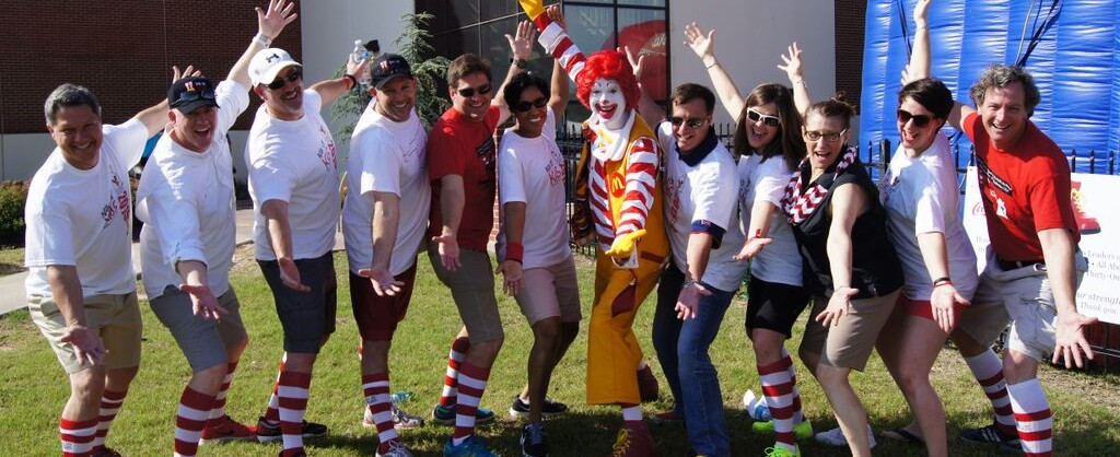 Ronald McDonald House Charities Oklahoma City Board of Directors posing with Ronald McDonald wearing red & white striped socks