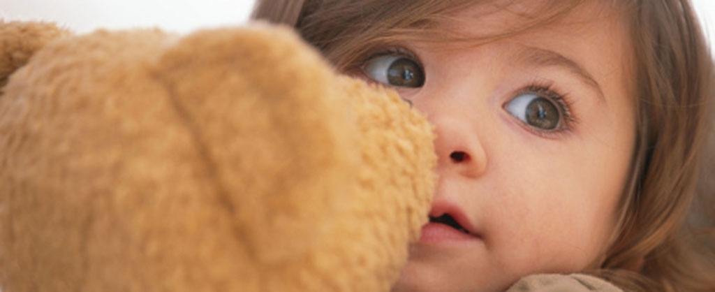 A little girl holding her teddy bear