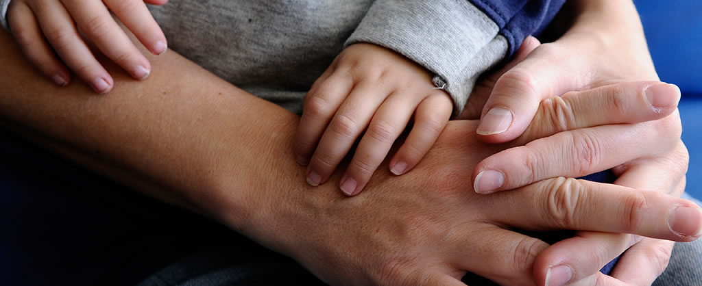 A baby's hand grabbing an adult hand
