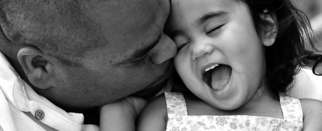 A dad kissing his toddler daughter