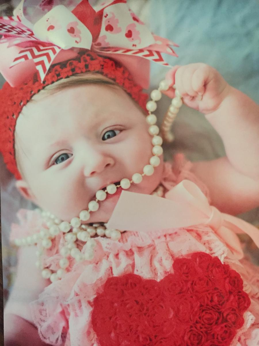 Baby girl dressed in a very frilly headband and dress playing with a string of pearls