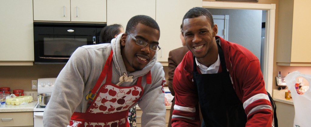 Two young men with aprons inside a kitchen smiling at the camera