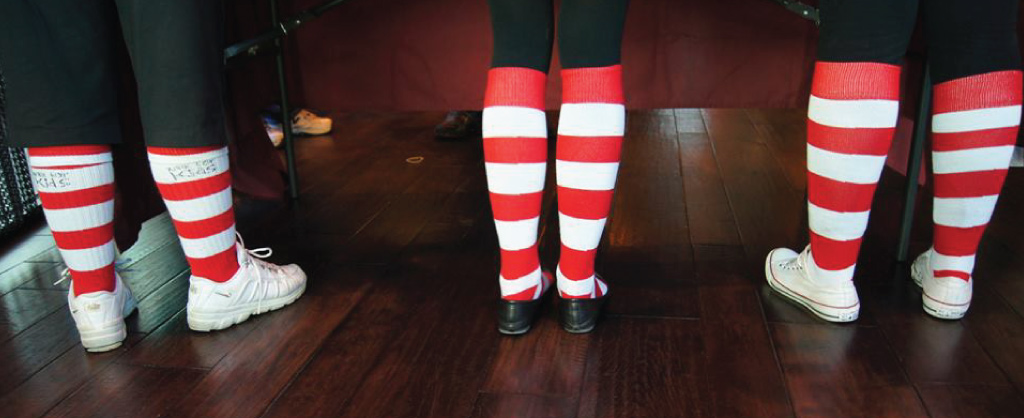 Three pair legs wearing red & white striped socks